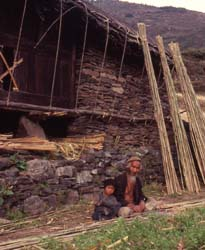 Splitting bamboo into strips to weave a roof matting